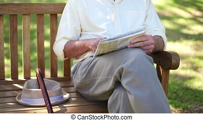 Retired man reading a newspaper sitting on a park bench