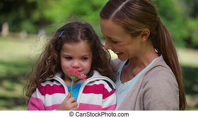 Mother and daughter smelling a flower in a park