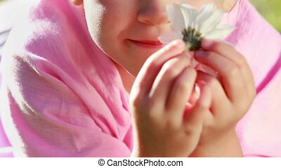 Peaceful little girl smelling a flower in the countryside