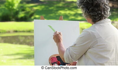 Happy mature woman drawing on a canvas in the countryside