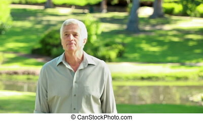 Peaceful mature man standing while looking at the camera in...
