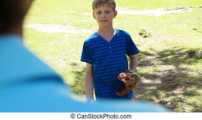 Smiling boy playing with a baseball with his father