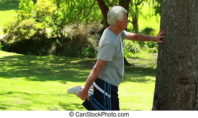 Relaxed mature man doing stretches in a parkland