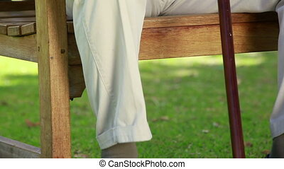 Mature man sitting on a wooden bench in the countryside