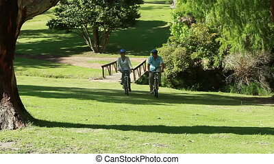 Happy couple riding their bikes together in a park