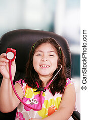 Cute little girl is playing doctor with stethoscope, isolated over white