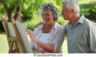 Smiling mature man looking at his wife who is painting in...