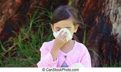 Smiling brunette girl blowing her nose