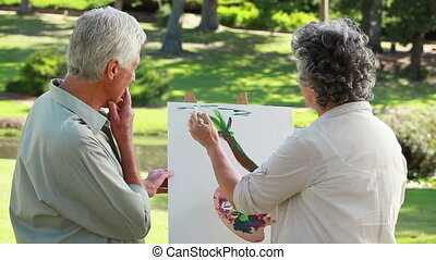 Mature couple standing in front of a canvas in the...