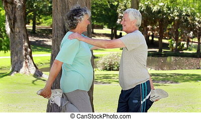 Smiling retired couple doing stretching exercises in a...