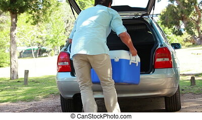 Rear view of a man placing his cooler in his car in a...