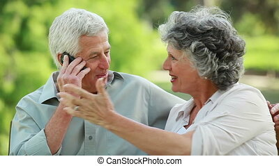 Mature couple using a cellphone together in a parkland
