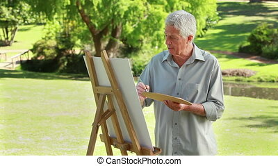 Serious mature man painting on a canvas in a parkland