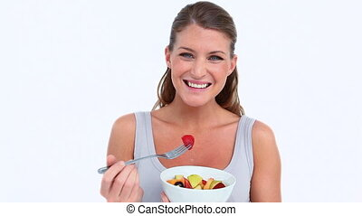 Smiling woman eating a fruits salad against white background