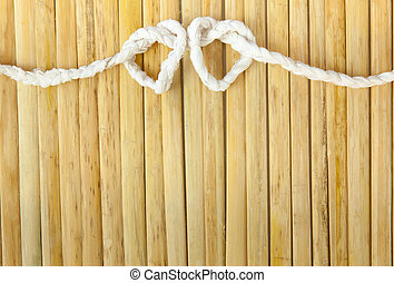 Rope in the shape of heart isolated on wood background
