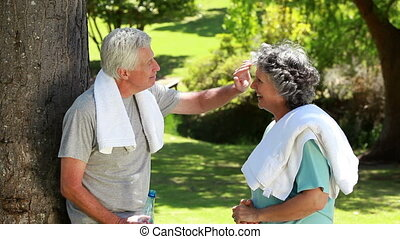 Mature couple wiping their foreheads with towels in the...