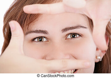 Pretty adult woman looking through a frame made by her hands.