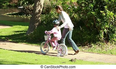 Smiling woman helping her daughter to ride a bike in a...