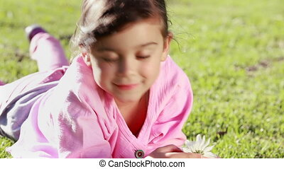Little girl holding a beautiful flower while lying on the...