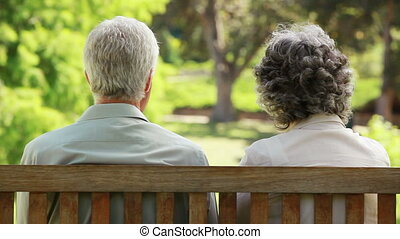 Mature people talking while sitting on a bench in the...