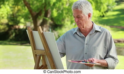 Smiling mature man holding a paint palette in a parkland