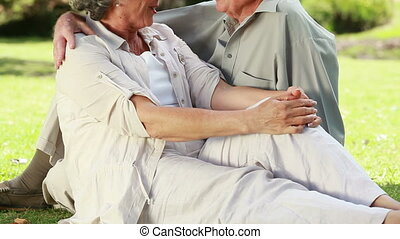 Mature couple talking together while sitting on the grass in...
