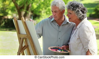 Smiling couple standing in front of a wooden easel in the...