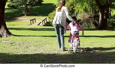 Rear view of a woman helping her daughter to ride a bike in...