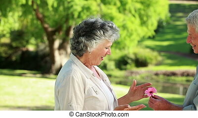 Smiling mature woman being given a flower