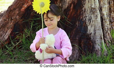 Smiling girl playing with a flower and a teddy bear