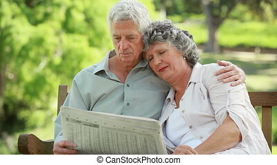 Mature man reading a newspaper while embracing his wife in a...