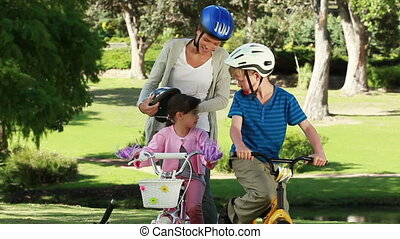 Smiling mother fastening the helmets of her children