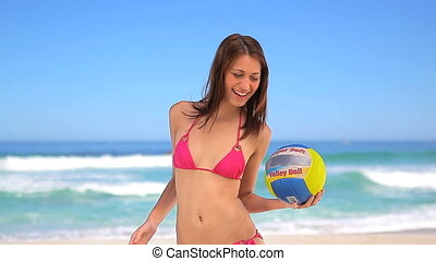 Happy brunette woman playing with a beach ball in front of...