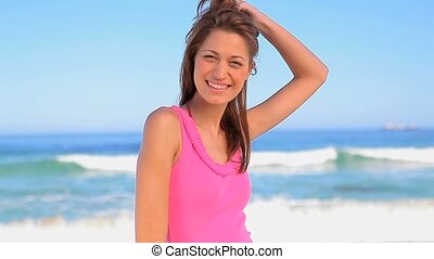 Happy woman placing her hands on her hips on the beach in...