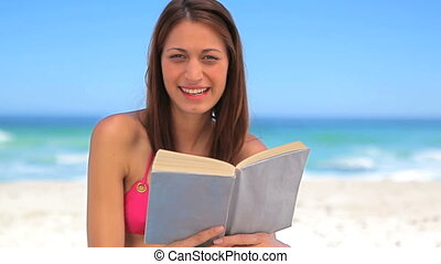 Smiling brunette enjoying the sun while holding a book on...