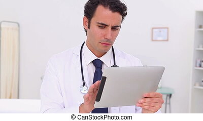 Serious doctor using a touchscreen