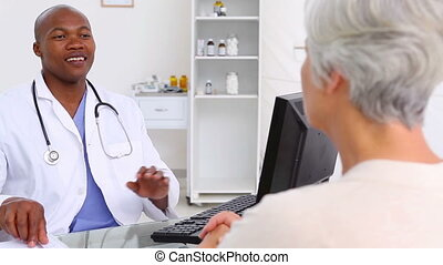 Mature woman explaining her pain to a doctor in his office