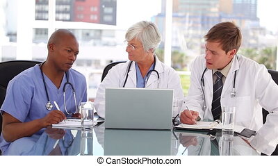 Mature doctor talking with two colleagues in a bright room