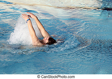 young man swimming backstroke in pool
