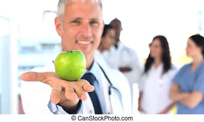 Smiling practitioner showing a green apple in a bright room