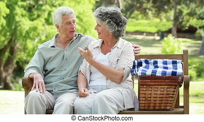 Happy mature people sitting on a bench in the countryside