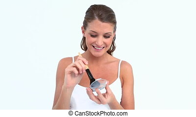 Happy woman putting blush on her face against white...