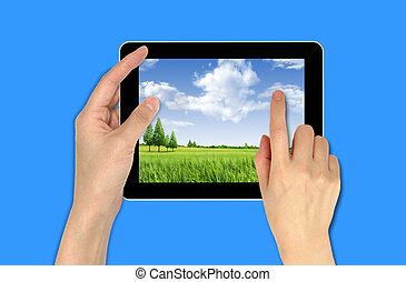 a male hand holding a touchpad with landscape wallpaper