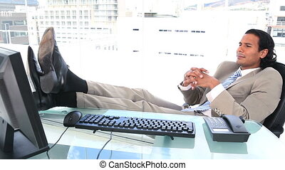 Happy businessman the feet on his desk