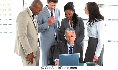 Colleagues helping a businessman with his laptop in a bright...
