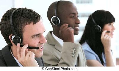 Smiling call centre agent working with his colleagues in a...