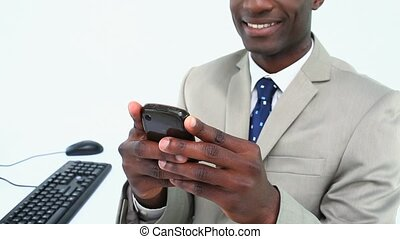 Smiling man text-messaging against white background