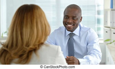Hiring - Smiling businessman interviewing a young woman for...