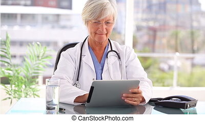 Smiling practitioner holding a tablet computer in a bright...