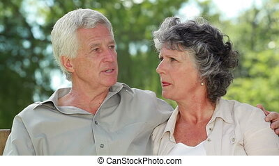 Happy mature couple talking while sitting on a wooden bench...